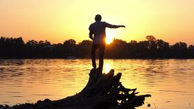 Young man stands on the tree roots on a lake bank in slo-mo. An impressive view of a young man who stands on tree roots on a forest lake bank at a splendid stock video footage