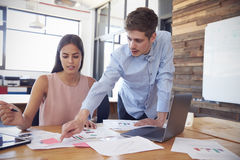 Young man stands working with a woman at her desk in office stock image