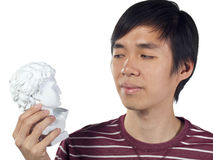 Young man stares at Roman bust in his hand Stock Image