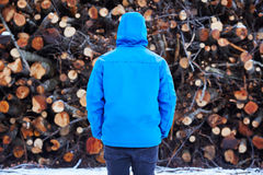 Young man staring at log stack Stock Images