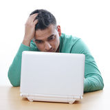 Young man staring at netbook Stock Photo