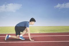 Young man in start position to run. While crouched in the track Royalty Free Stock Images