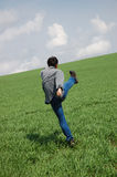 Young man start running. On the green grass hill Royalty Free Stock Image