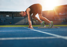 Young man on starting position about to run. Young man on starting position ready for running. Male athlete in the starting blocks on sports track about to run Stock Photography