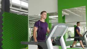 Young man starting to running on treadmill stock video