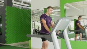 Young man starting to running on treadmill and listening to music on headphones stock video footage