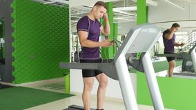 Young man starting to running on treadmill and listening to music on headphones stock footage