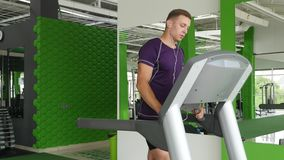 Young man starting to running on treadmill and listening to music on headphones stock video