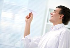 Young man starts  paper airplane Stock Image