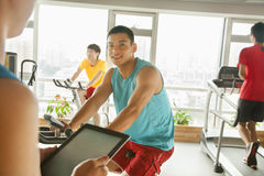 Young man on stationary bike exercising with his personal trainer Royalty Free Stock Images