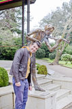 Young man and statue of violinist. Portrait of smiling man taking picture with metal statue of a violinist Royalty Free Stock Photos