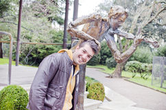 Young man and statue of violinist Royalty Free Stock Photo