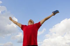 Young man staying with raised hands. Against blue sky Royalty Free Stock Photos