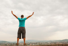 Young man staying with raised hands Stock Images