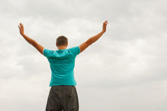 Young man staying with raised hands Stock Photos