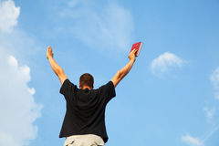 Young man staying with raised hands Stock Photo