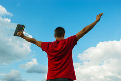 Young man staying with raised hands. Against blue sky Royalty Free Stock Photography