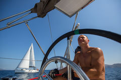 Young man steers a sailing boat at the yacht regatta Royalty Free Stock Image