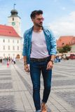 Young man stepping forward on street looks down to side. Young casual man stepping forward on city streets looks down to side, full length picture royalty free stock photo