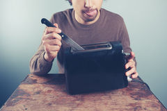 Young man sticking knife in toaster Stock Photography