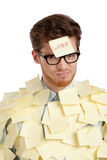 Young man with a sticky note on his face, covered with yellow sticky notes Royalty Free Stock Photo