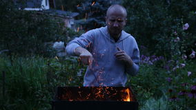 Young man stirring coals in the brazier stock footage