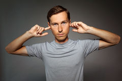 Young man stopped his ears with fingers. Stock Images