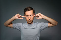 Young man stopped his ears with fingers. Royalty Free Stock Photo