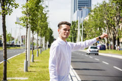 Young man stopping a taxi cab Royalty Free Stock Image