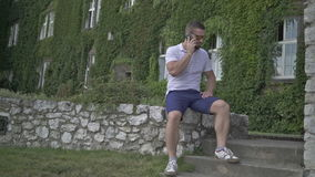 Young man stops over for the call, outdoor. stock footage