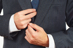 Young man straighten his business suit closeup Royalty Free Stock Images