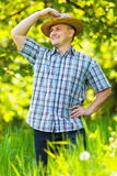 Young man in straw hat outdoor in a garden. Young man in straw hat and checkers shirt outdoor, in an orchard Stock Photography