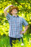 Young man in straw hat outdoor in a garden. Young man in straw hat and checkers shirt outdoor, in an orchard Stock Images