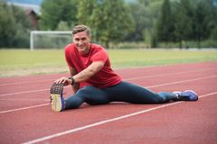 Young Man Is Streching Outdoors. Portrait of Fit and Sporty Young Man Doing Stretching in the Park Stock Photo
