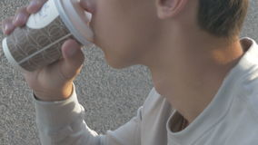 A young man on the street drinking coffee, coarsely porter stock video footage