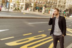 Young man on the street with mobile phone. Young man on the phone Royalty Free Stock Image