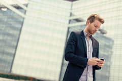 Young man on the street with mobile phone Royalty Free Stock Image