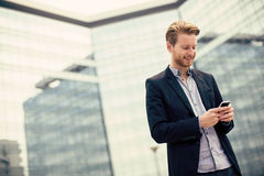 Young man on the street with mobile phone Stock Photography