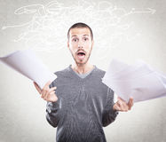 Young man stressed holding papers Stock Photos