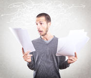 Young man stressed holding papers Stock Photo