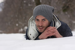 Young man stretched out on the snow Stock Images
