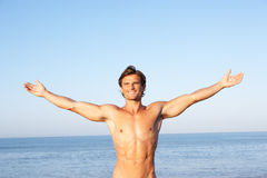 Young man stretching on beach Stock Images