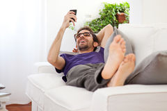 Young man stretching comfortably on couch Royalty Free Stock Photos