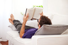 Young man stretching comfortably on couch and reading a book Royalty Free Stock Photos