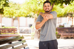 Young man stretching his arms before working out. Portrait of a handsome young man stretching his arms and warming up before going jogging in a park and smiling Royalty Free Stock Photo