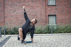 Streching in a city enviroment. Outdoor training. A young man is stretching his body on the streets of the city. Fit lifestyle Stock Photo