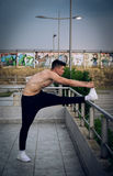 Young man stretching his leg after a heavy workout. Wearing trac royalty free stock image