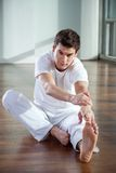 Young Man Stretching Leg At Gym Royalty Free Stock Photos