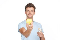 Young man stretching out hand with apple. Royalty Free Stock Photography