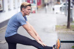 Young man stretching outdoors in the street Stock Photos
